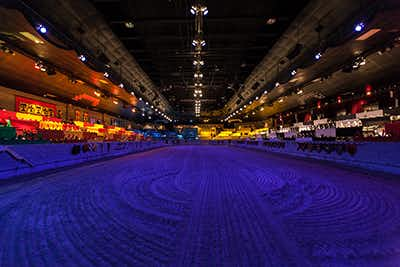 Empty, dimly lit Medieval Times dirt floor arena, with bright yellow-hued lighting in the far distance.