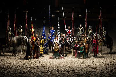 A group photo of many knights and the king from the Medieval Times show stand together in the center of the arena, with the dirt floor beneath their feet, raising their brightly colored flags. Men are kneeling in front of the king, while others sit upon horses, all praising the king.
