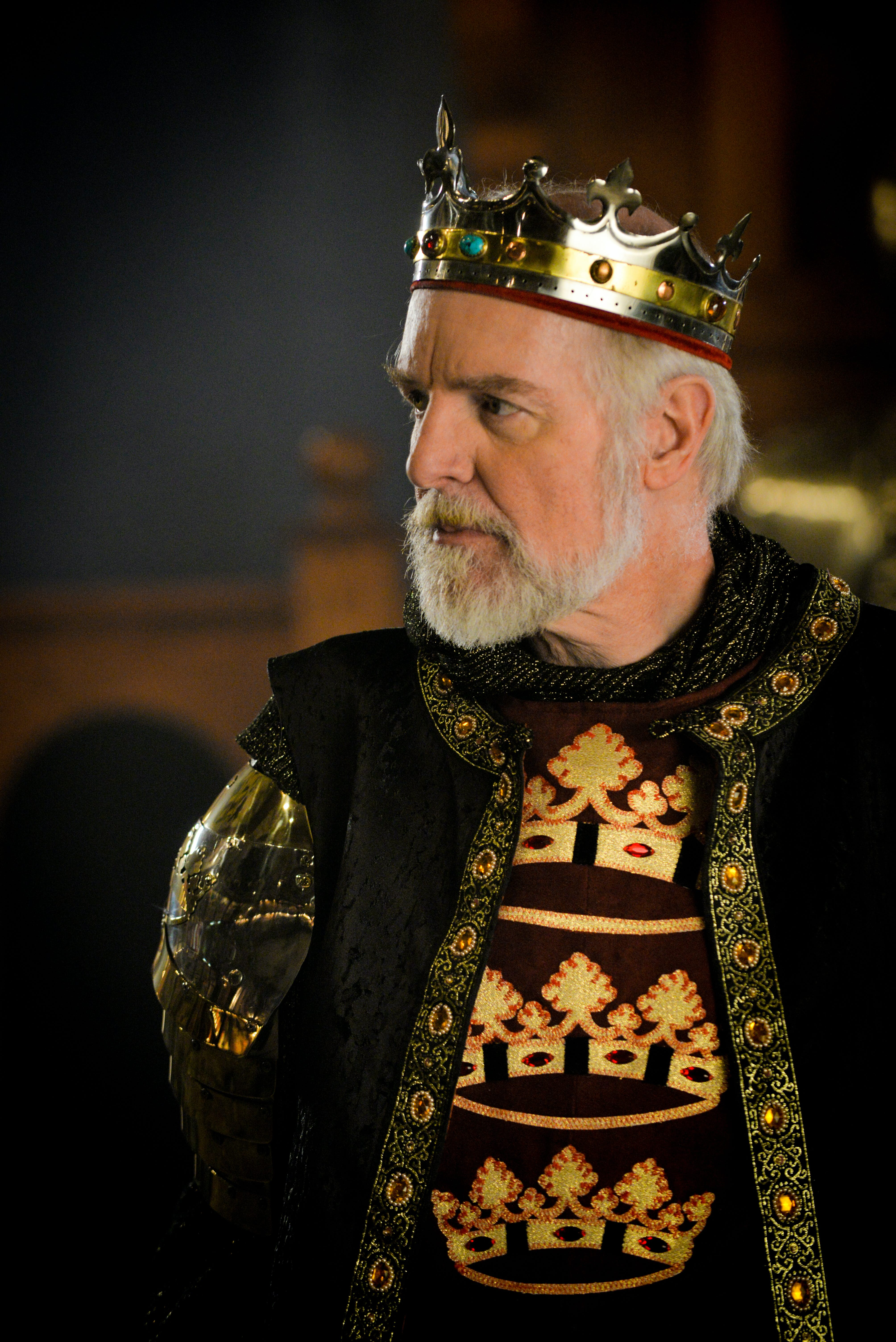 Photo of King wearing his crown with jewels, and displaying his wealth by wearing dark green velvets imported from italy.