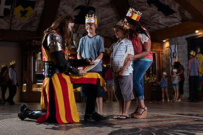 Knight dressed in yellow and red, kneeling down in front of four children wearing Medieval Times crowns signing autographs.