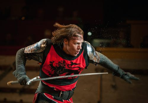 The Red Knight running with his sword forward, and breeze blowing through his hair.