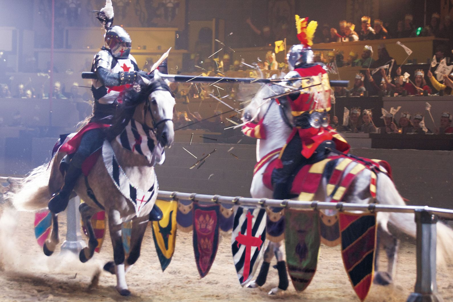 Two knights jousting on horses making impact with lances in arena